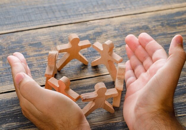 Business success concept on wooden background high angle view. hands protecting wooden figures of people.